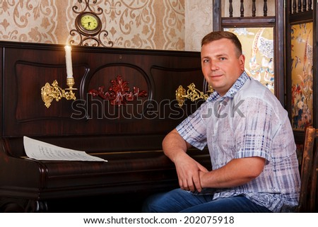 Virtuoso playing piano. Side view of handsome young men playing piano  - stock photo