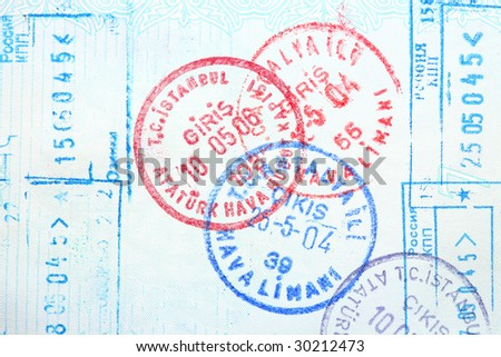 Visa entry and exit stamps in a passport - stock photo