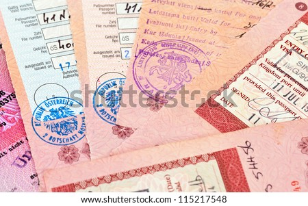 Visa entry and exit stamps in passport - stock photo