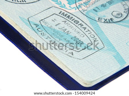 visa stamps in open passport page - stock photo