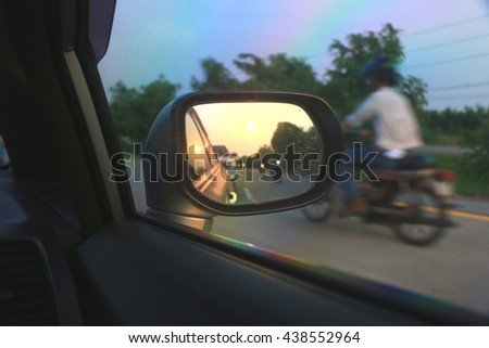 visibility in the wing mirror of the car while a driving the car on the road with last sun light before night time.