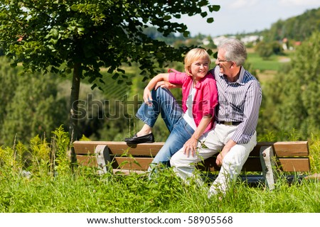 Visibly happy mature or senior couple outdoors arm in arm deeply in love, both are sitting on a bench - stock photo