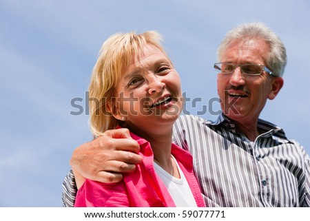 Visibly happy mature or senior couple outdoors arm in arm deeply in love, looking down from a blue sky