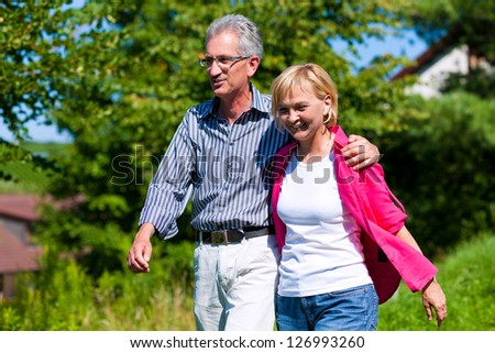 Visibly happy mature or senior couple outdoors arm in arm having a walk - stock photo