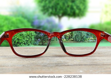 Vision concept. Glasses on green tree and bushes background