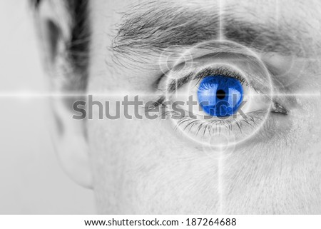 Vision concept with a greyscale image of a mans eye with a crosshair focused on his iris which has been selectively colored blue. - stock photo