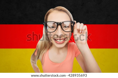 vision, education, national and people concept - happy smiling young woman or teenage girl eyeglasses over german flag background
