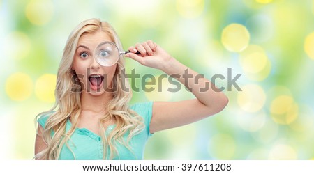 vision, exploration, investigation, education and people concept - happy smiling young woman or teenage girl looking through magnifying glass over summer green lights background - stock photo