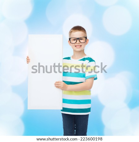 vision, health, advertisement and people concept - smiling little boy in eyeglasses with white blank board over blue background - stock photo