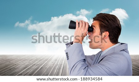 Visionary businessman looking to the future against cloudy sky background - stock photo