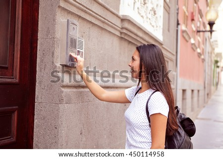 Visiting young girl with a back pack buzzing the intercom at a wooden door wearing her hair loose, casual clothing