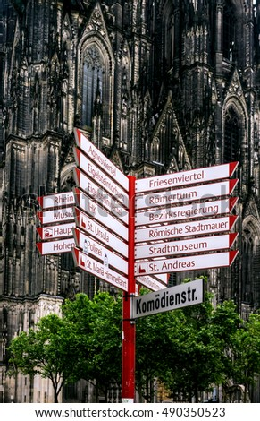 visitor direction sign in cologne, germany with cathedral in background