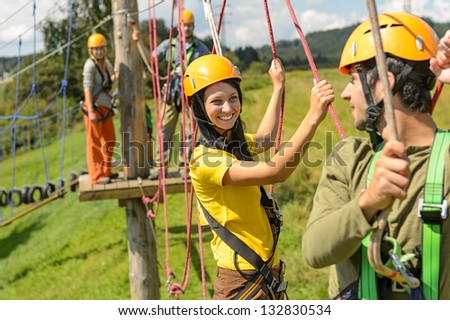 Visitors in adventure park clambering with ropes wear protective helmets