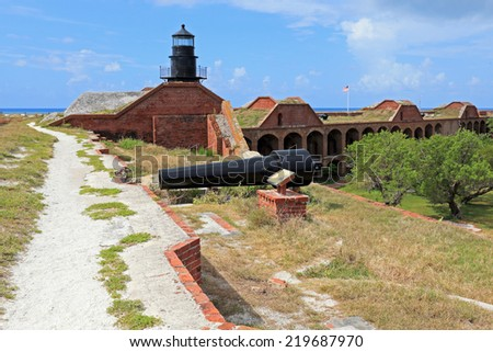 Visitors to Fort Jefferson can stroll along the rooftop path to see the old cannons and the lighthouse. - stock photo