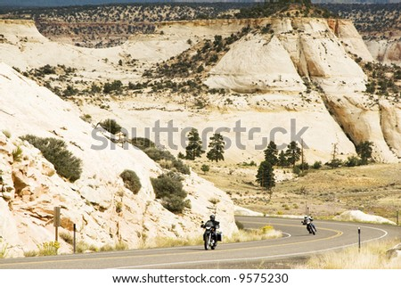 visitors travel on motorcycles along a section of scenic byway in the Grand Staircase-Escalante National Monument in Southern Utah. - stock photo