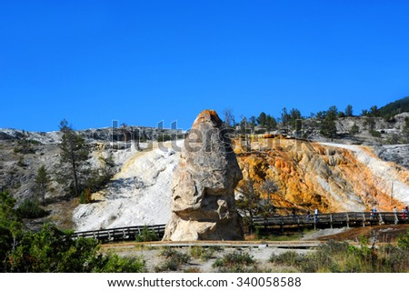 Visitors walk boardwalk and admire Liberty Cap at Mammoth Hot Springs in Yellowstone National Park. - stock photo