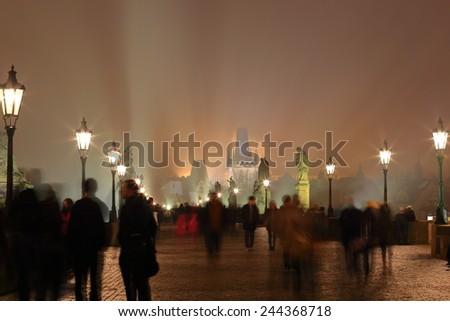 Visitors walking on the Charles bridge in foggy autumn night, Prague, Czech Republic - stock photo