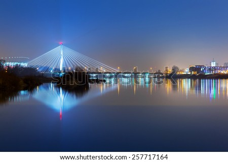 Vistula river scenery with cable-stayed illuminated bridge in Warsaw, Poland - stock photo