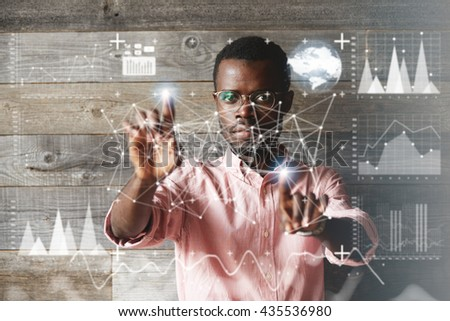 Visual effect. Worldwide interface. Concentrated African American programmer working on a project, making graphics and diagrams, touching futuristic screen interface . Selective focus on the face - stock photo