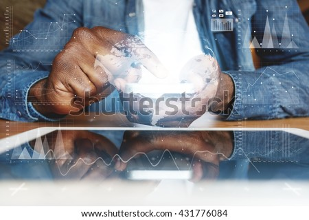 Visual effects. Graphic icons. People and future technology concept. Cropped shot of African American young man in denim jacket, touching electronic gadget with reflective touchscreen surface - stock photo