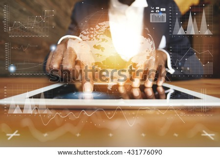 Visual effects. Worldwide connection technology interface. Young businessman sitting at the wooden table wearing formal suit, using futuristic electronic device for working at the cafe. Film effect - stock photo
