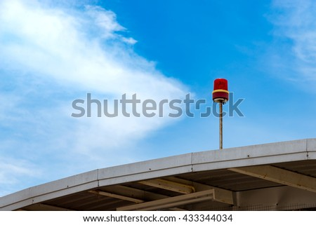 Visual signalling fire alarm light or siren on roof with blue sky on background - stock photo