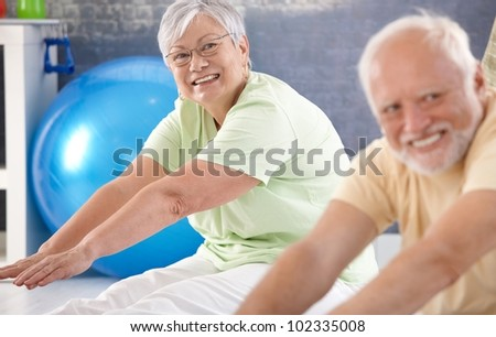 Vital old lady exercising in the gym. - stock photo