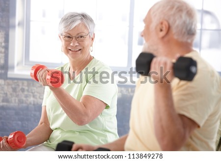 Vital senior couple exercising in the gym. - stock photo