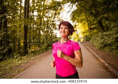Vital senior woman jogging in park on summer evening - stock photo