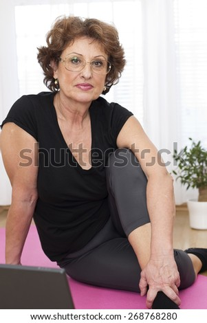 Vitality senior brown haired woman sitting on the parquet floor  in front of laptop after exercising  and looking at camera. - stock photo