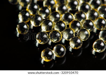Vitamin A (Retinol) Oil Capsules on Black Background - stock photo