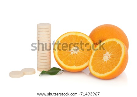 Vitamin c tablet stack with orange fruit whole and in half with leaf sprig, over white background.
