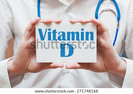 Vitamin D written on a card in doctors hands - stock photo