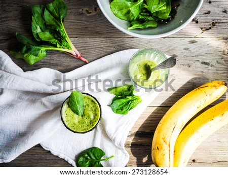 Vitamin green smoothie with spinach leaves, banana and peanut milk, clean eating, on gray wooden background - stock photo