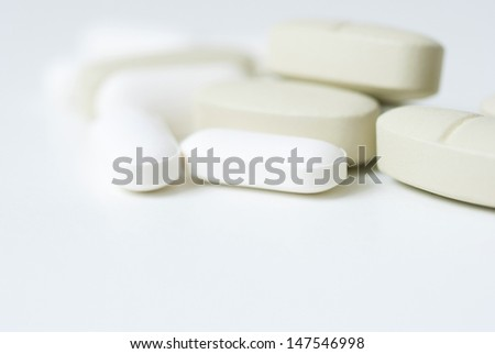 vitamin pills on white tablet