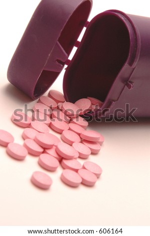 vitamin pills with focus on pills in the mouth of the bottle to draw the eye in