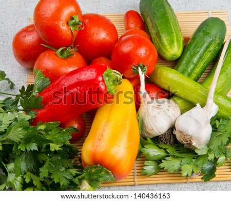 Vitamin set of vegetables from the lred ripe tomatoes, orange and yellow peppers and purple garlic with green sprigs of fresh