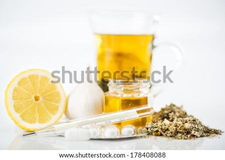 Vitamins and pills for treatment Cold And Flu. Lemon, tea, honey, garlic and Thermometer on white background. Selective focus. - stock photo