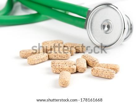 Vitamins and stethoscope against white background - stock photo