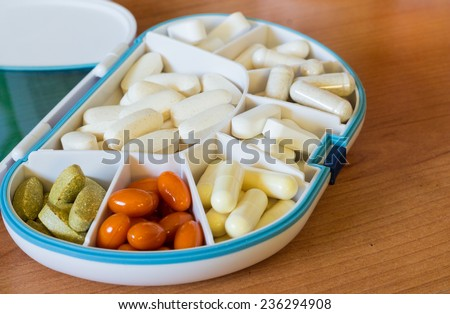 Vitamins and Supplements in a Pillbox - stock photo