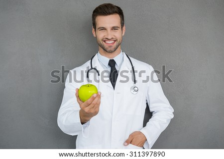 Vitamins are important for health. Cheerful young doctor in white uniform stretching out green apple and smiling while standing against grey background - stock photo