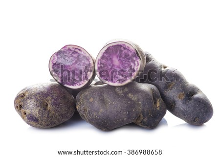Vitelotte or blue-violet potatoes isolated on a white background - stock photo