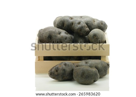 Vitolette noir or purple potato(truffe de chine) in a box / crate. On a white background - stock photo