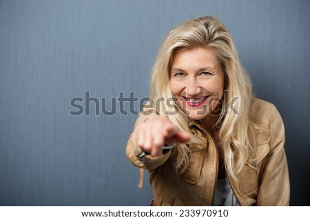 Vivacious attractive blond middle-aged woman pointing at the camera with a beaming playful smile, blackboard background with copyspace - stock photo