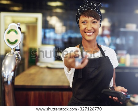 Vivacious attractive young African American bar tender handing back a bank card after processing payment conceptual of a small business owner - stock photo