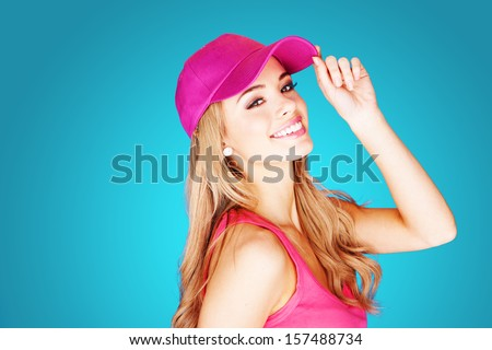 Vivacious beautiful blond woman in summer fashion wearing a trendy pink peak cap and top over a blue background - stock photo