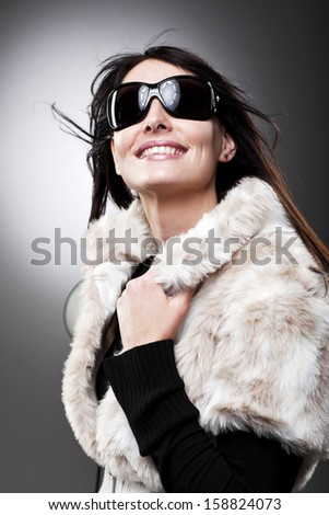 Vivacious beautiful woman in sunglasses and a fur jacket smiling happily as she looks upwards with her hand to the collar of her jacket