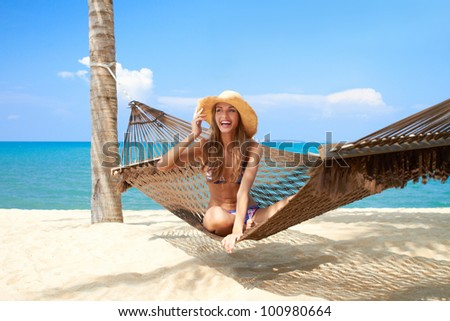 Vivacious beautiful woman wearing a straw sunhat relaxing in a hammock tied to a palm tree on a tropical island resort - stock photo