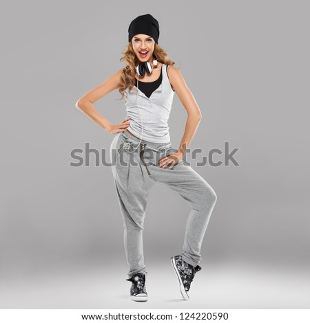 Vivacious beautiful young student in casual track pants and a cap with a set of headphones aound her neck laughing at the camera - stock photo