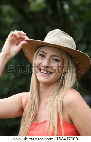 Vivacious beautiful young woman in a trendy wide brimmed hat touching her hand to the brim in greeting while walking outdoors in the park - stock photo